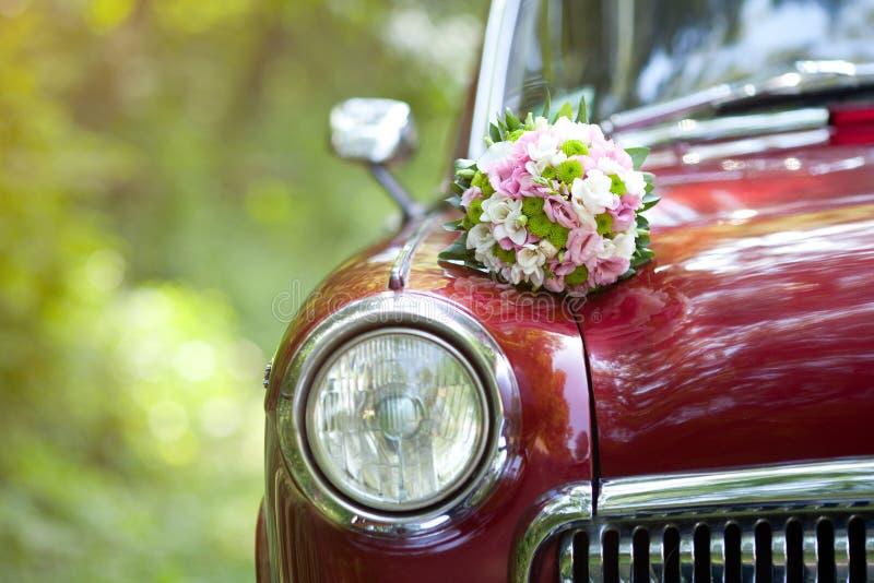 Bröllopbukett på tappningbröllopbilen royaltyfri fotografi