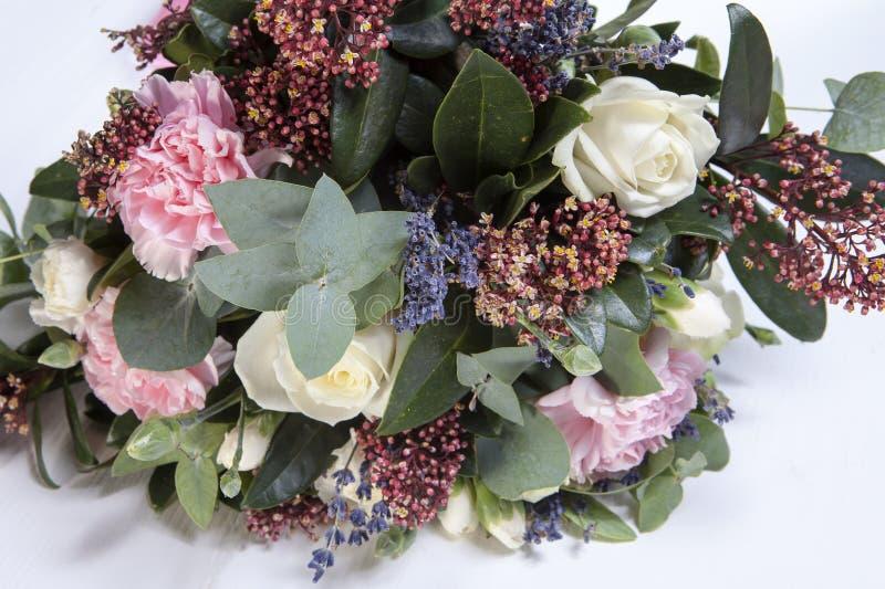 Bröllopbuketten av en brud från en ros, en rosa nejlika, eukalyptus på en trätabell arkivbild
