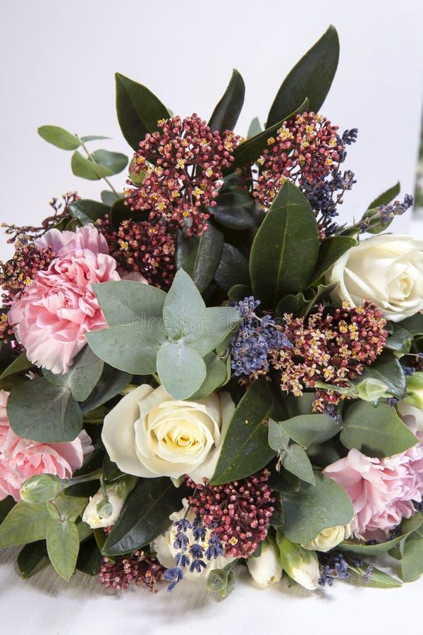 Bröllopbuketten av en brud från en ros, en rosa nejlika, eukalyptus på en trätabell royaltyfria bilder