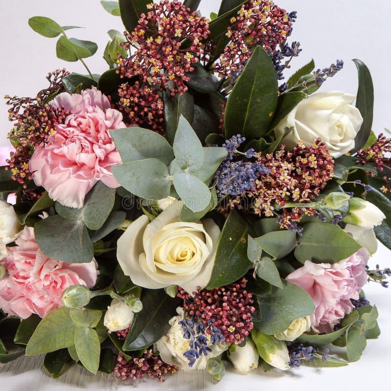 Bröllopbuketten av en brud från en ros, en rosa nejlika, eukalyptus på en trätabell royaltyfria foton