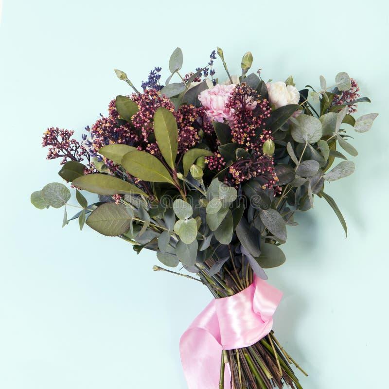 Bröllopbuketten av en brud från en ros, en rosa nejlika, eukalyptus på en trätabell royaltyfri foto
