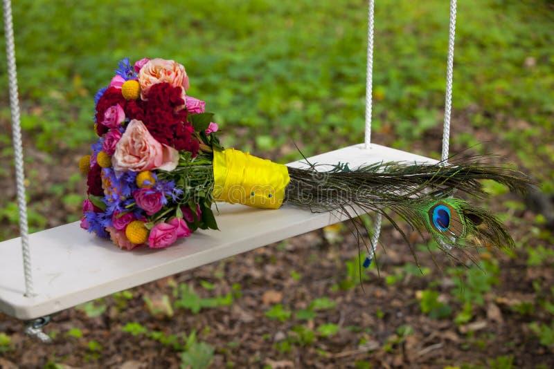 Bröllopbuketten av rosa färger, röda, blåa och gula blommor och påfågeln befjädrar på gunga royaltyfri foto