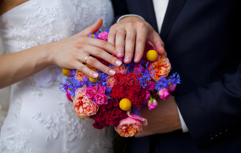Bröllopbuketten av rosa rosor, blått som är röda, guling blommar och händer av bruden och brudgummen arkivbilder