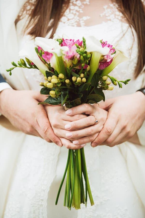 Bröllopbuketten räcker in av brud royaltyfri foto
