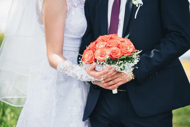 Bröllopdag - brud och brudgum som rymmer en bukett royaltyfri foto