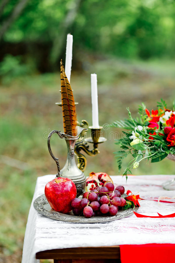 Bröllopdekor med frukt, blommor, stearinljus och en fasanfeathe arkivbilder