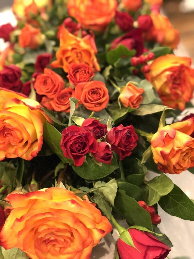 Bröllopdekor: orange och röda rosor, tabellgarneringnygifta personer, presidium arkivfoton
