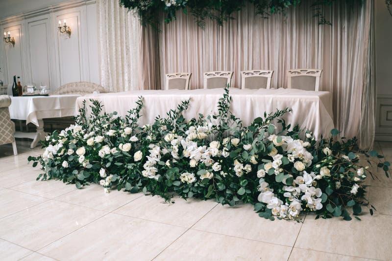 Bröllopdekoren, tillbehör, orkidér, rosor, eukalyptuns, en bukett i en restaurang, presiderar tabellinställningen royaltyfria bilder