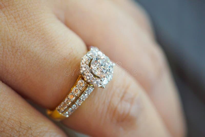 Bröllopdiamantcirkel på kvinnafingret royaltyfria bilder