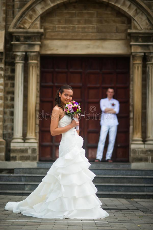 Bröllopfoto med bruden och brudgummen Härlig ung brud som poserar på bakgrunden av brudgummen och katolska kyrkan royaltyfri bild