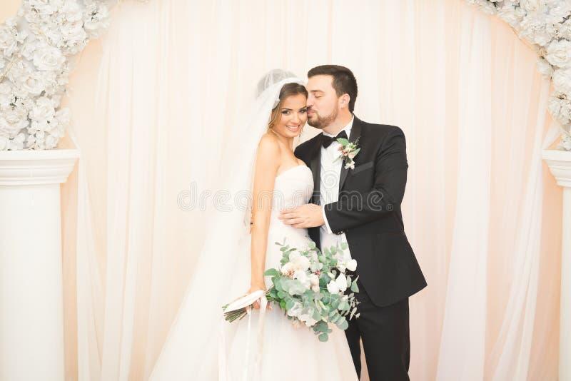 Bröllopfotoforsen av nygifta personerna kopplar ihop i ett härligt hotell som poserar nära fönster royaltyfria foton