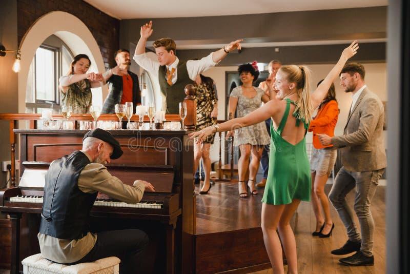 Bröllopgäster som har gyckel med pianot arkivbild