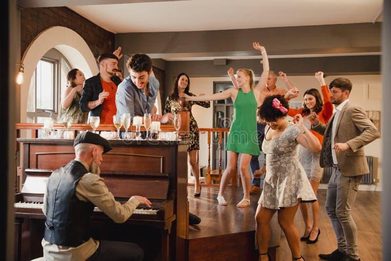 Bröllopgäster som har gyckel med pianot fotografering för bildbyråer