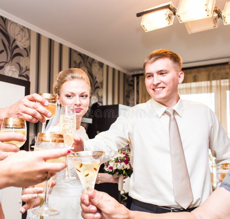 Bröllopgäster som klirrar exponeringsglas royaltyfria bilder
