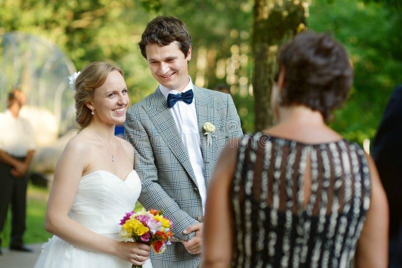 Bröllopgäster som rostar bruden och brudgummen royaltyfri bild