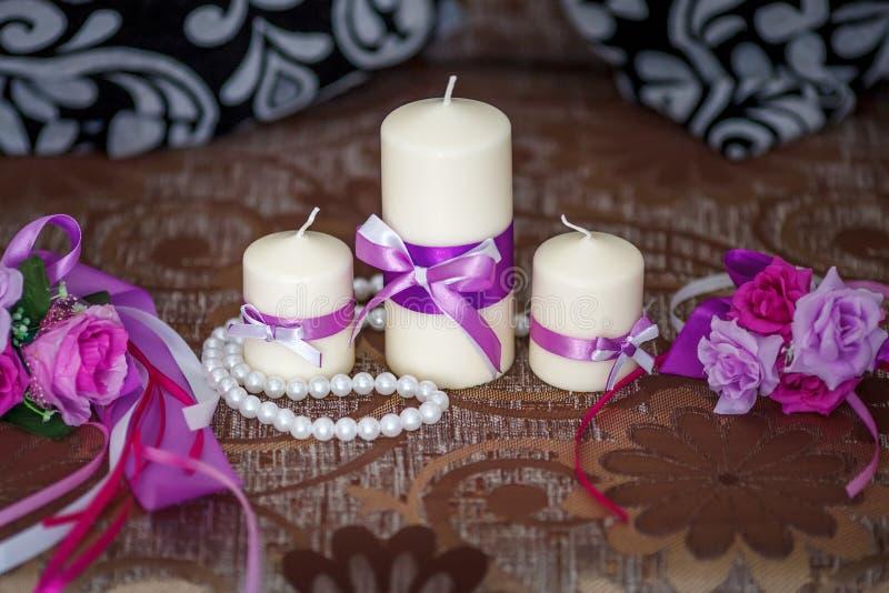 Bröllopgarnering, stearinljus med det purpurfärgade bandet, selektiv fokus royaltyfri bild