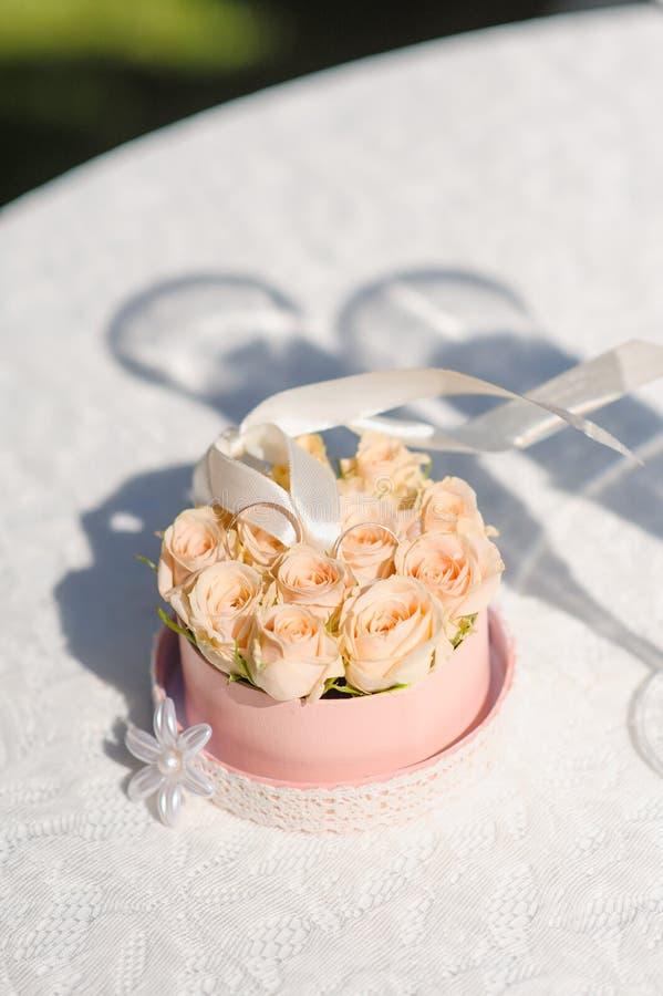 Bröllopgarneringbegrepp Ställning för två guldbröllopcirklar i rosor arkivfoton