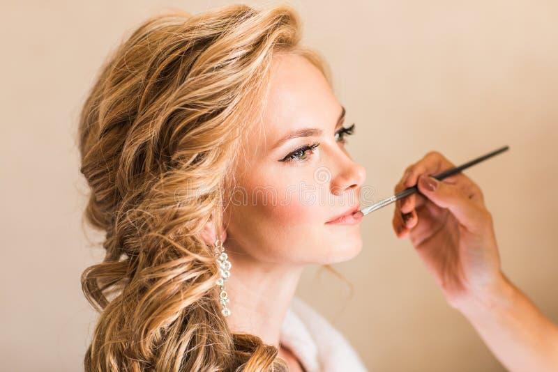Bröllopmakeupkonstnär som gör ett smink för brud Härlig sexig modellflicka inomhus Blond kvinna för skönhet med lockigt hår arkivbild