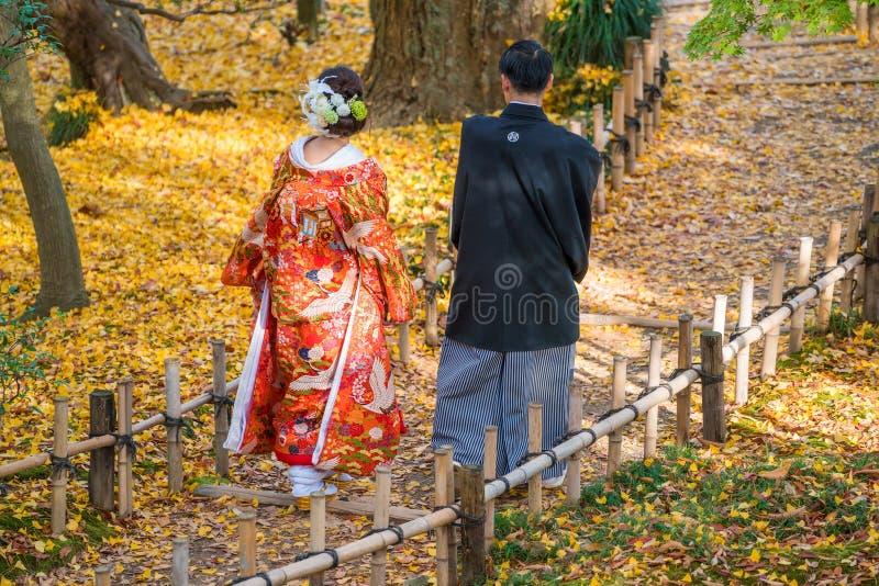 Brölloppar i den traditionella klänningen som går i den Kenrokuen trädgården, Kanazawa arkivfoto