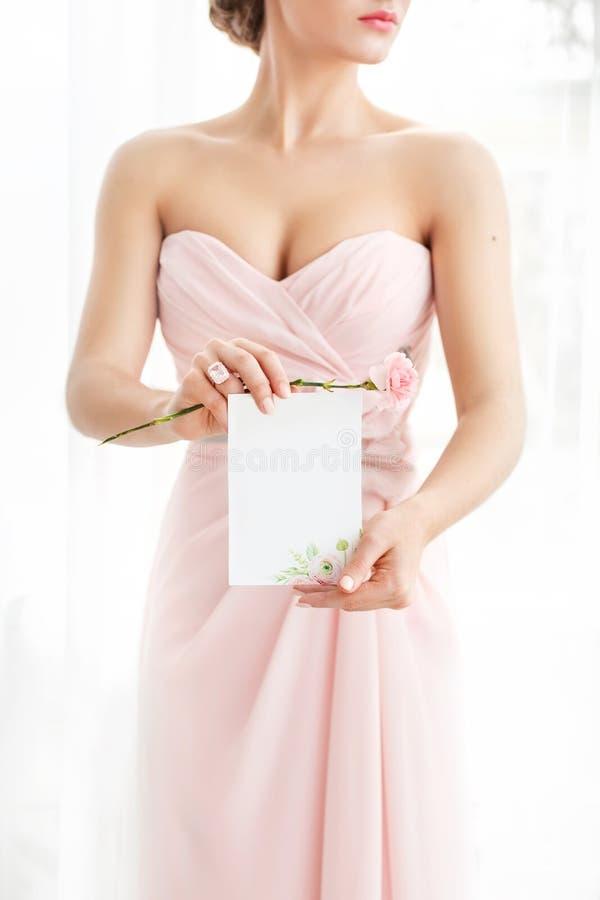 Brölloppolygraphy Inbjudan i händerna av kvinnor royaltyfria bilder