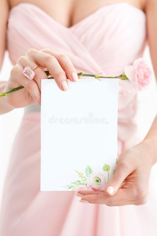 Brölloppolygraphy Inbjudan i händerna av kvinnor royaltyfri bild