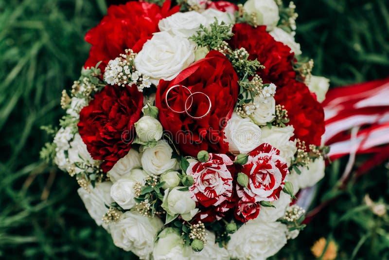 Bröllopring i Rose, gifter du dig med mig bröllopsringar på en bröllopsbukett royaltyfria bilder
