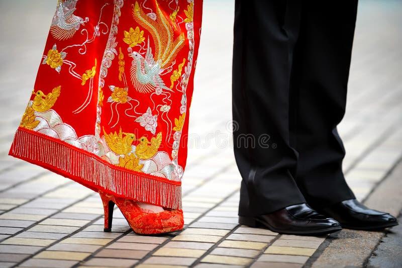 Bröllopsklänning för traditionell kines och västra smoking arkivfoto