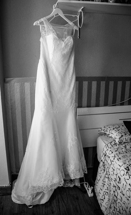 Bröllopsklänning och brudgum som förbereder sig på fönstret fotografering för bildbyråer