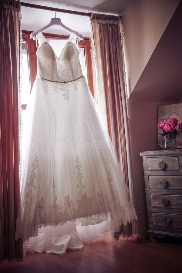 Bröllopsklänning som hängs i ett sovrum fotografering för bildbyråer