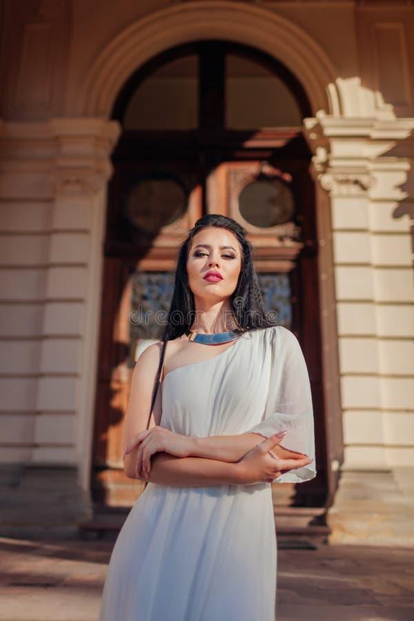 Bröllopsklänning, tillbehör och smycken för härlig kvinna bärande vit på forntida arkitekturbakgrund utomhus arkivfoto