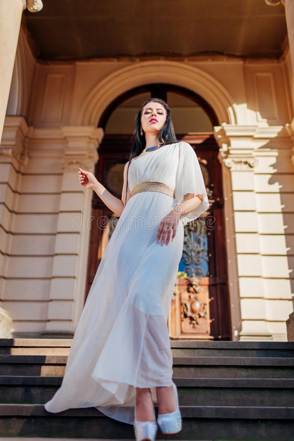Bröllopsklänning, tillbehör och smycken för härlig kvinna bärande vit på forntida arkitekturbakgrund utomhus royaltyfria foton