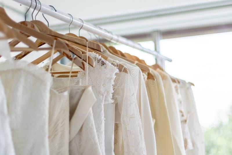 Bröllopsklänningar som hänger på hängare i bröllop, shoppar royaltyfria foton
