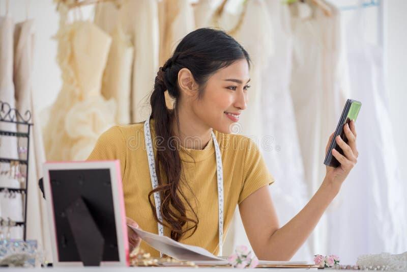Bröllopsklänningformgivare som arbetar med den smarta telefonen, i att gifta sig salongen av modelagret royaltyfria bilder