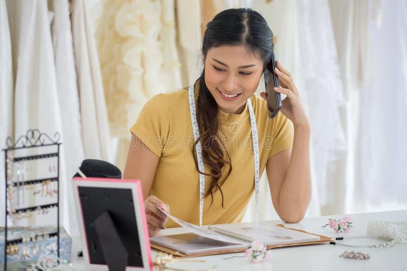 Bröllopsklänningformgivare som arbetar med den smarta telefonen, i att gifta sig salongen av modelagret fotografering för bildbyråer
