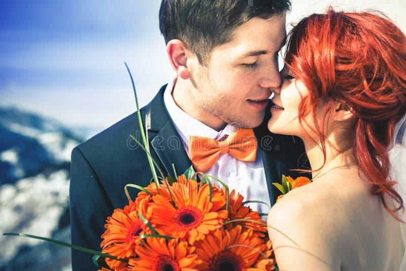Bröllopsnowboarderspar att gifta sig precis på bergvintern royaltyfria foton