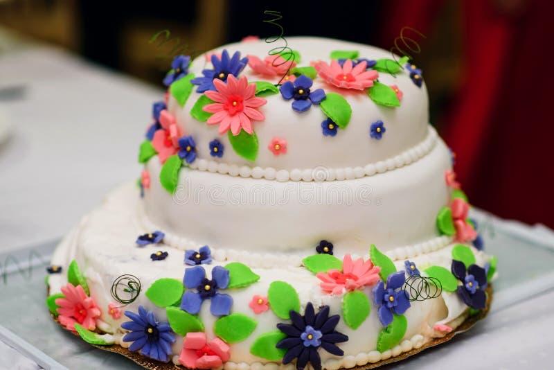 Bröllopstårta i vit söt glasyr med färgrika blommor royaltyfria bilder