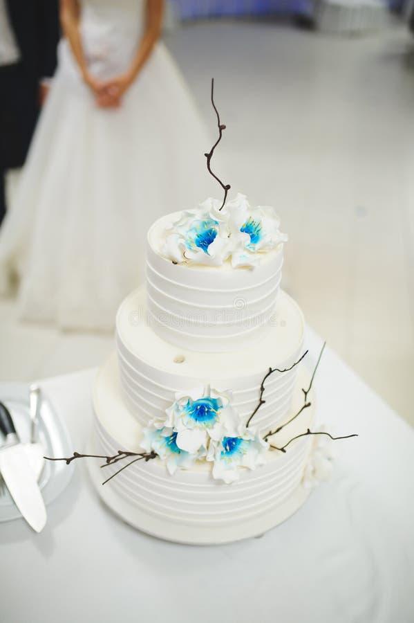 Bröllopstårta med blåa blommor arkivfoton