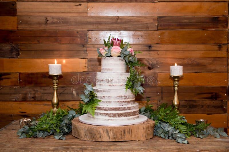 Bröllopstårta med blommor och stearinljus royaltyfria foton