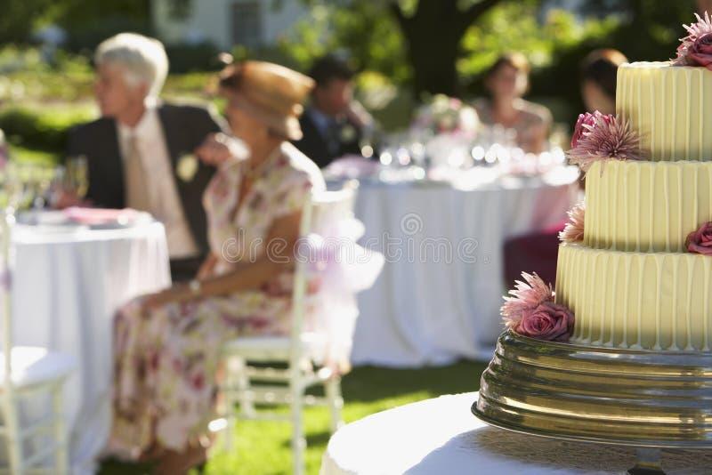 Bröllopstårta med gäster i bakgrund fotografering för bildbyråer