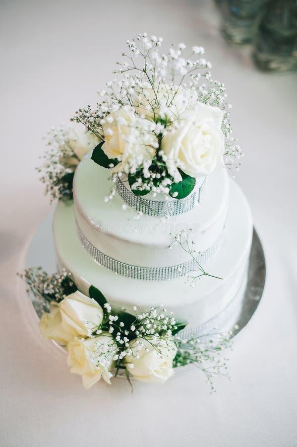 Bröllopstårta med gul beige turkosgräsplan för blommor fotografering för bildbyråer