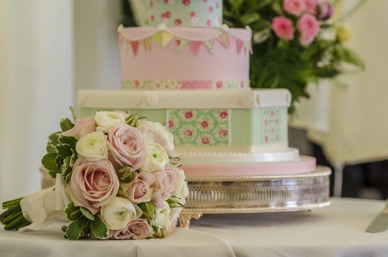Bröllopstårta och bukett royaltyfri foto