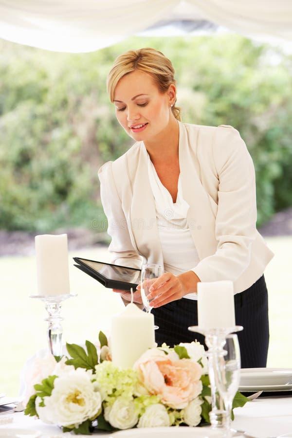 Bröllopstadsplanerare Checking Table Decorations i stort festtält royaltyfri fotografi