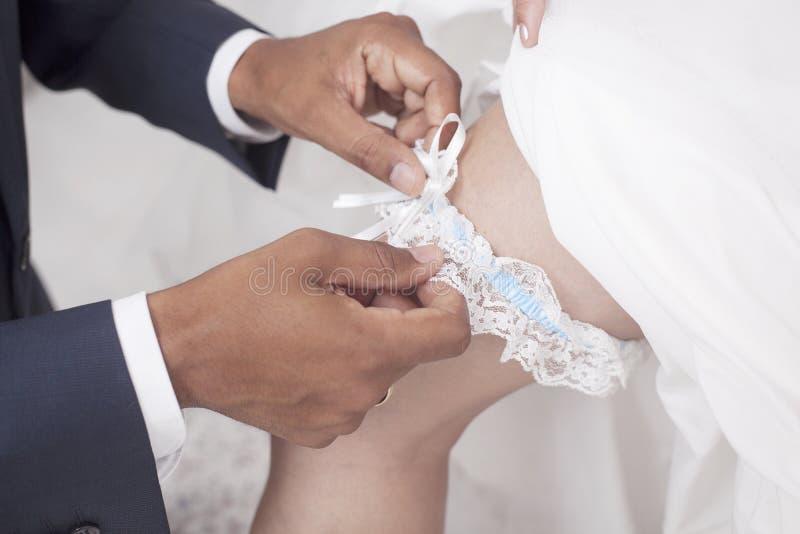 Brölloptradition som bär en strumpeband royaltyfria bilder