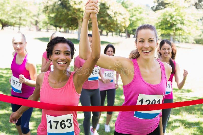 Bröstcancerdeltagare som korsar mållinjen på loppet royaltyfria bilder