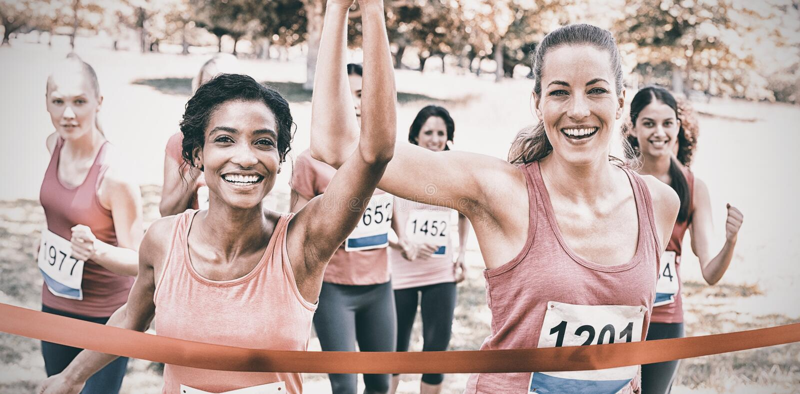 Bröstcancerdeltagare som korsar mållinjen på loppet arkivfoto
