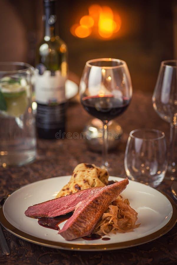Bröstet för den grillade anden med kål och pannkakan tjänade som på den vita plattan med exponeringsglas av vin, vintern och säso royaltyfri fotografi