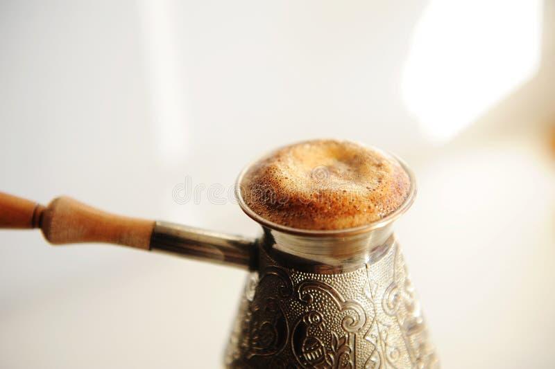 Bröstkaffe i koppscezve Högt stigande skum nära Vit bakgrund royaltyfri bild
