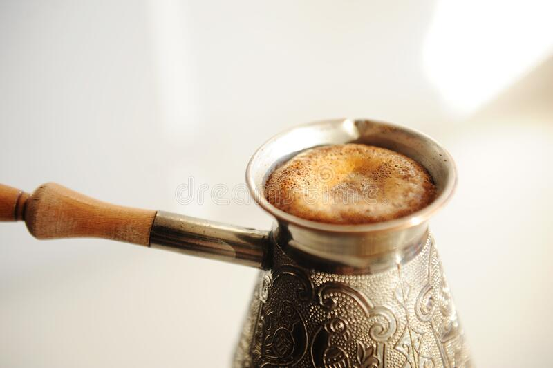 Bröstkaffe i koppscezve Stigande skumbildning Vit bakgrund royaltyfri bild