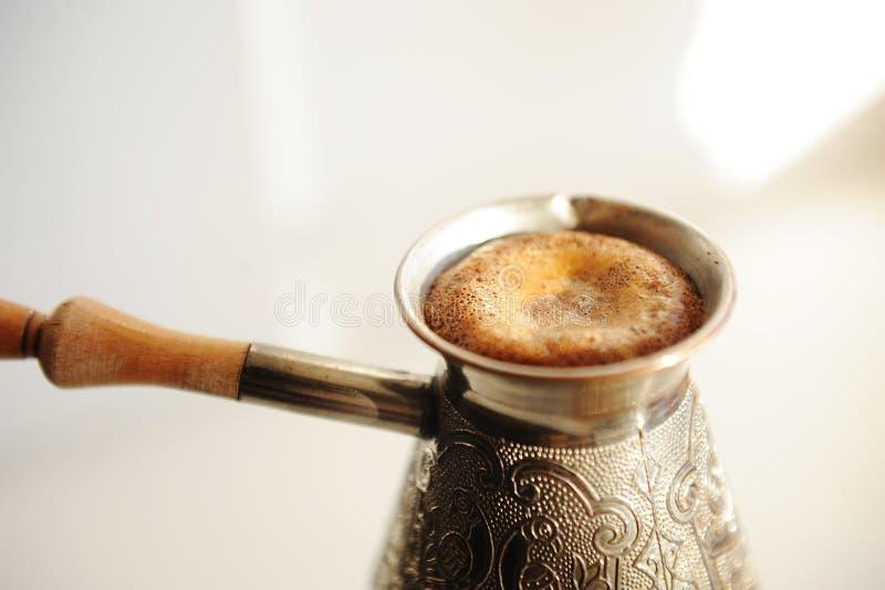 Bröstkaffe i koppscezve Stigande skumbildning Vit bakgrund royaltyfria bilder