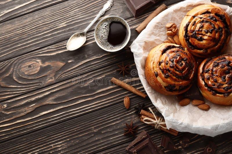 Brötchen mit Zimt und Schokolade auf einem braunen hölzernen Hintergrund stockfotos